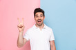 Quadro Image of positive man 30s having stubble showing peace sign with happy smile, isolated over colorful background