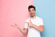 Image of handsome man 30s having stubble pointing fingers aside at copyspace, isolated over colorful background