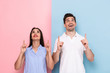 Image of happy couple in casual wear smiling and gesturing fingers upward, isolated over colorful background
