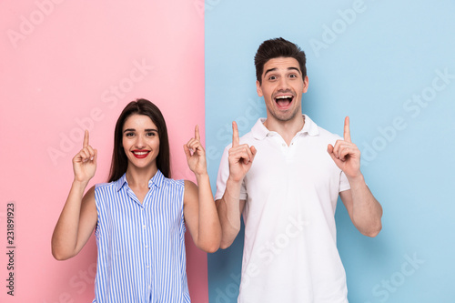 Foto Murales Image of optimistic couple in casual wear smiling and gesturing fingers upward, isolated over colorful background