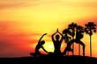 Leinwandbild Motiv Silhouette of woman practicing yoga on the beach at sunset