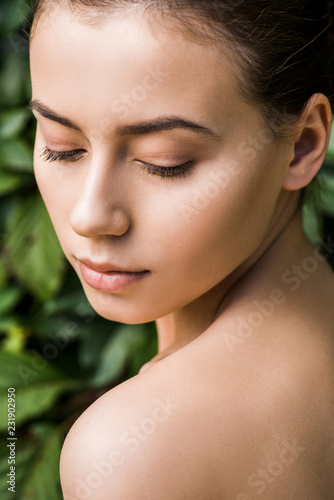 młoda kobieta z zamkniętymi oczami na tle zielonych liści