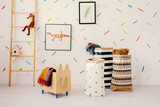 Wooden crate and patterned bags in child's room interior with fox on ladder next to posters. Real photo - 231908784
