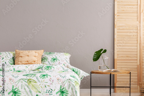 Leinwandbild Motiv Leaf pattern on duvet in stylish bedroom interior with wooden screen and coffee table with glass vase with monster leaf, real photo with copy space on grey empty wall