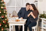 romantic couple drinking tea with cookies, talking and looking photo album - 231910975