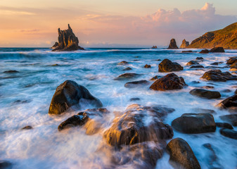 beautiful Benijo beach in Tenerife, waves crashing against boulders during sunset © Mike Mareen