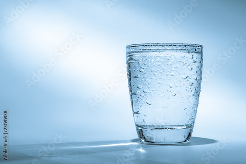 Glass with water on blue background - 231919138