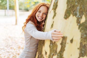 pretty redhead woman hugging a large tree