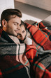 high angle view of happy young couple relaxing on couch and covering with plaid