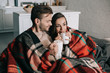 happy young couple with mugs of cocoa with marshmallow relaxing on couch and covering with plaid