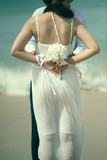 Back side of asian woman hold white flower in white dress by sea with man,valentine concept. - 231924947