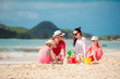 Family of four making sand castle at tropica beach