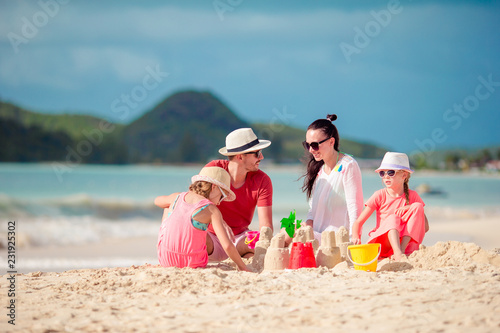 Foto Murales Family of four making sand castle at tropica beach
