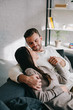beautiful young couple relaxing on couch and holding hands at home