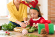 Cute preschooler girl wearing reindeer antlers and her mother making christmas wreath in living room. Christmas decoration family fun concept.