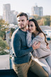 beautiful young couple embracing on rooftop and looking somewhere