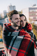 happy young couple covering in plaid and looking away with blurred city on background