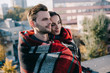 smiling young couple covering in plaid and looking away with blurred city on background