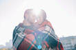 beautiful young couple covering in plaid and cuddling with sun shining behind
