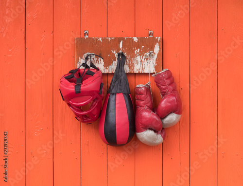 old red boxing gloves on the orange wall