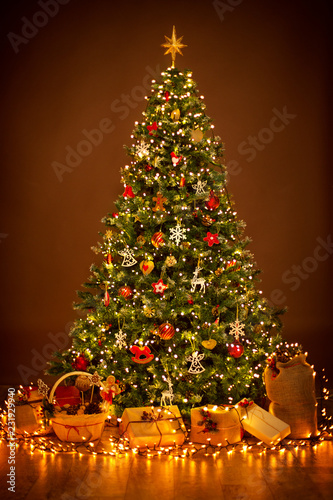 Foto Murales Christmas Tree lighting in night, Xmas Decorations Hanging on Chritmastree, Star Top Light and Present Gifts