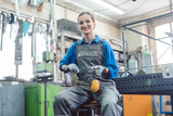 Female mechanic sitting in metal workshop looking and smiling into camera - 231930730
