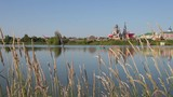 View of the rural landscape with the lake and the church. Calm summer morning in Russia - 231935541