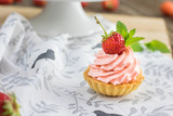 Detail on a Strawberry tart with strawberry whipped cream with one strawberry and mit leaf