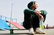 Leinwandbild Motiv Full length portrait of unrecognizable teenager sitting on skateboard while chilling at extreme park outdoors, copy space