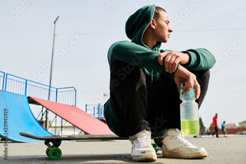 Foto Murales Full length portrait of unrecognizable teenager sitting on skateboard while chilling at extreme park outdoors, copy space