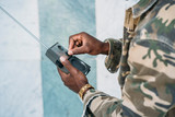 Man dressed as a camouflage with walkie talkie - 231948540