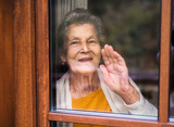 An elderly woman standing by the window, looking out. Shot through glass. - 231949965