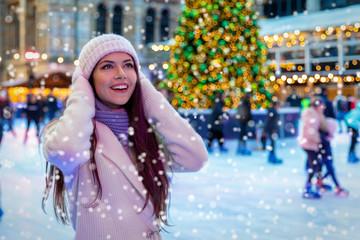 Junge Frau in winterlicher Kleidung auf einem Weihnachtsmarkt freut sich über den Schneefall