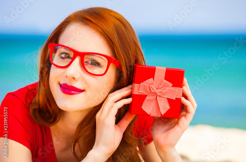 Foto Murales Redhead girl in the glasses with gift on the beach