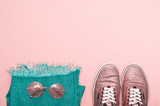 Bright shiny sneakers, glasses and jeans on a pastel pink background. Powder color - 231956117