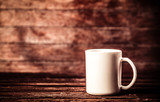 White cup of coffee on wooden table and background - 231956582
