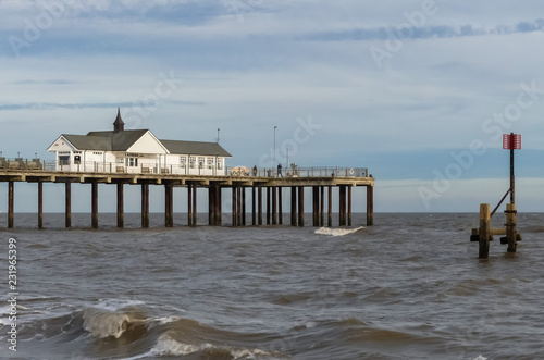 Landscape view of a vintage Pier, from the public beach, with metal groyne marker. Wave breaking on foreshore. Blue sky with horizontal cloud formation. England
