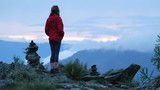Young woman in red jacket stands on the edge of the cliff and observes the valley at sunset. Altai, Russia. Hand held camera - 231971529