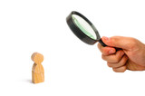 Magnifying glass is looking at a Wooden figurine of a man on a white background. A lonely man, minimalism. Place for text. Slide for presentation. - 231971707