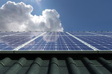 Solar panels modules on house roof with clear sky in background - 231974940