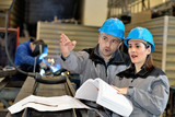 Metal factory manager pointing at something while talking to female apprentice - 231976191