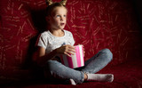 Children's cinema: One schoolgirl girl watches a movie at home on a big red sofa and eats a popkort from a red bucket. - 231979544