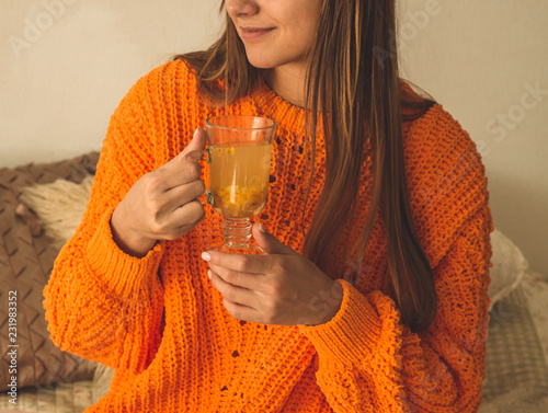 Leinwanddruck Bild Beautiful Happy Young Woman Drinking Cup Of Coffee Or Tea. In Bed in a bright orange sweater. Closeup Portrait Of Smiling Girl