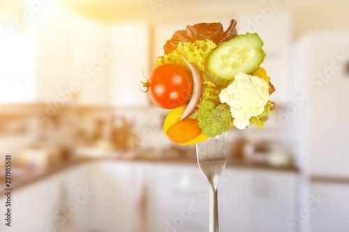 Leinwanddruck Bild Fresh variety vegetables on fork, soft blue background