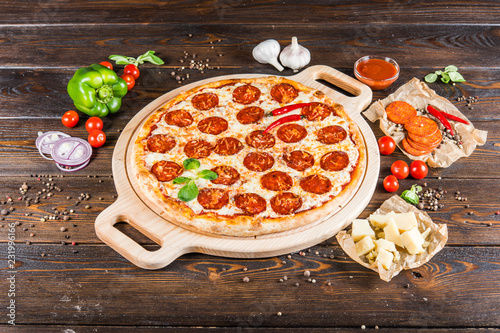 Leinwanddruck Bild Large spicy pizza with salami and pepperoni sausage on a round cutting board on a dark wooden background. Pizza Ingredients