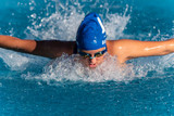 Female swimmer with arms out and pulling water as she speeds toward the finish line during butterfly stroke heat. - 232001167