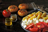 Italian pasta with feta and tomatoes. Spices and buns. Vegetarian lunch.