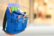 Leinwandbild Motiv Colorful school supplies in backpack on blurred background