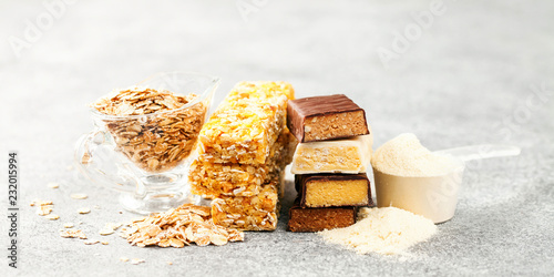 Leinwanddruck Bild Different Energy protein bars and oatmeal bars on grey background.   Set of energy, sport, breakfast and protein bars