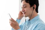 スマートフォンで音楽を聴く男性 - 232019306